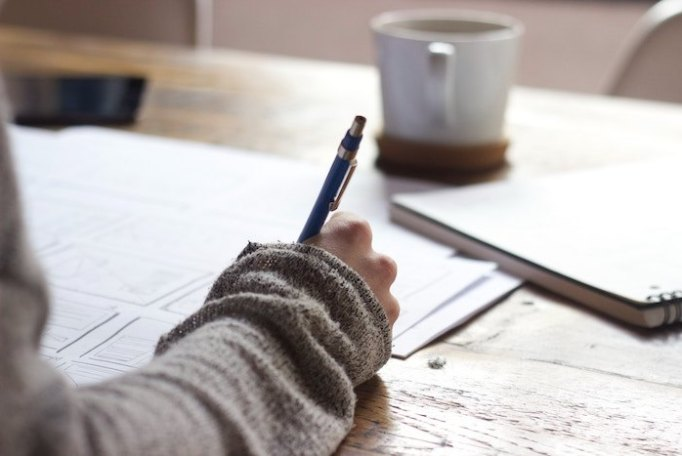 A woman is writing with a pen at a table covered with paper, notebooks, and a cup of coffee.