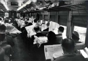 Black and white 20th century photograph of men reading newspapers on a train