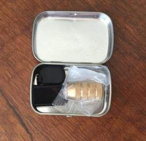Mini Altoids tin with brass bullet sharpener, USB dongle, and thumb drive